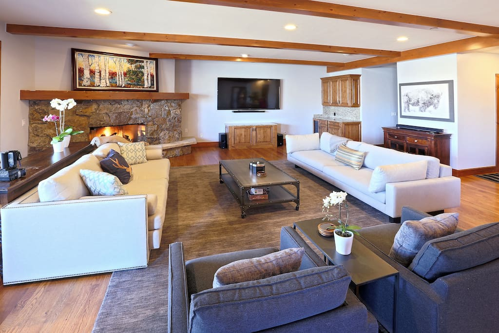 Large living room and gathering space includes wine and beer fridge, Sonos system, and large TV with Apple TV for movie nights.