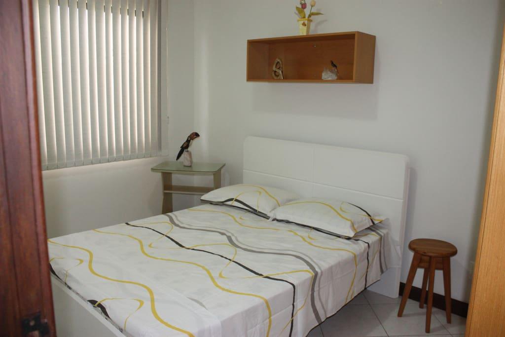 Quarto com cama de casal, mesa de cabeceira e banquinho