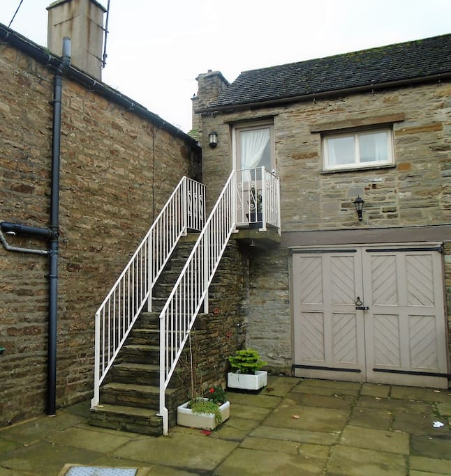 Parking in front of the garage. Entrance to the flat is up the stone steps.