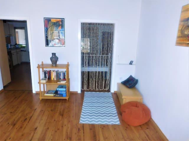 Wohnzimmer links  Tür zur Küche, rechts geht's ins Schlafzimmer, im Regal spannende Bücher auch über die Region und Spiele...