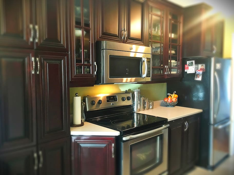 Stainless steel appliances and cherry wood cabinetry in a comfortable kitchen.