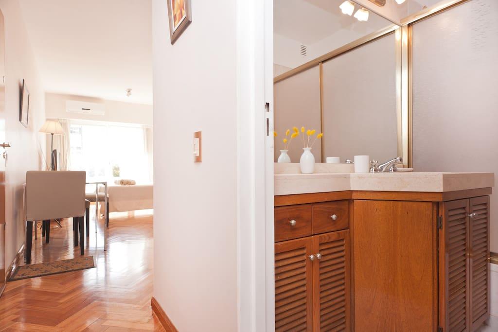 Baño: vanitory madera y mármol travertino