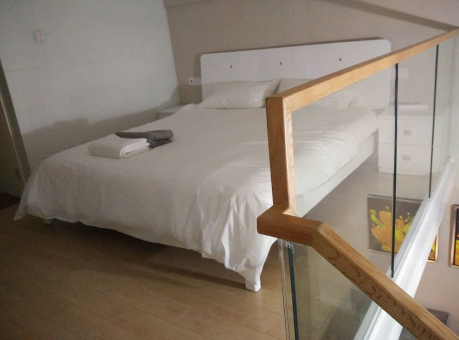 A few inches short of a king size bed (1.8 x 2 meters). Clean comfortable sheets. Open style loft.