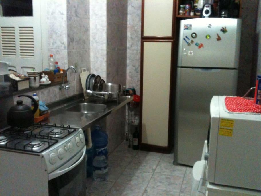 Cozinha com fogão, geladeira, micro-ondas, área de serviço com lava roupas.