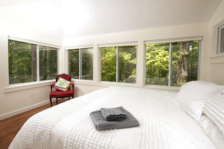 """Sleep in our """"treehouse"""" bedroom with windows that overlook Fernwood's 1 acre property."""