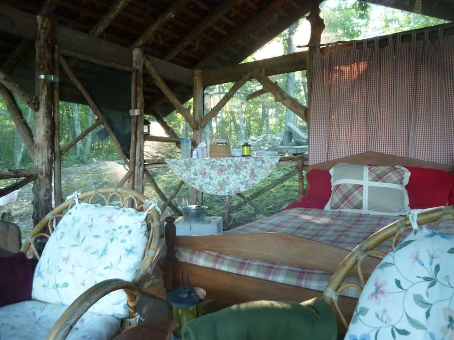 The screened cabin has a double bed and sitting area
