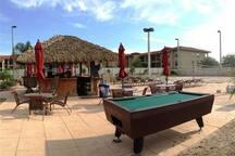 Tiki, pool, volleyball area, kiddie pool. Tiki, piscina, área de voleibol, piscina para niños.