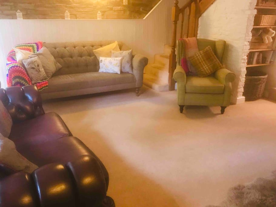 Spacious, cosy living area with comfy sofas and chair for unwinding and relaxation.
