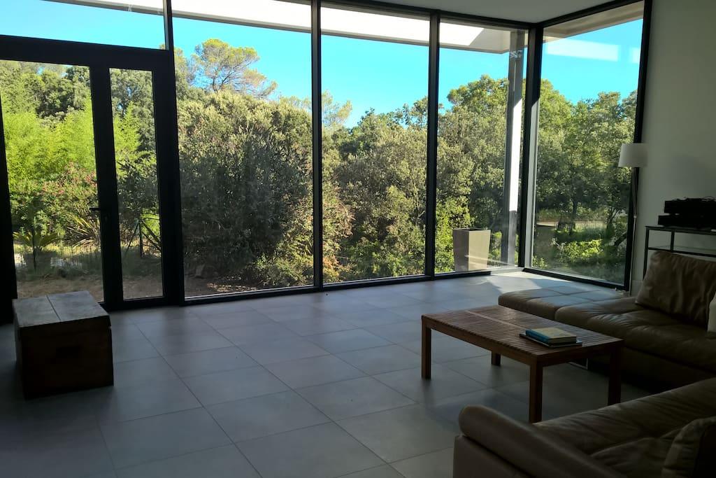 Salon avec mur vitré donnant sur la nature