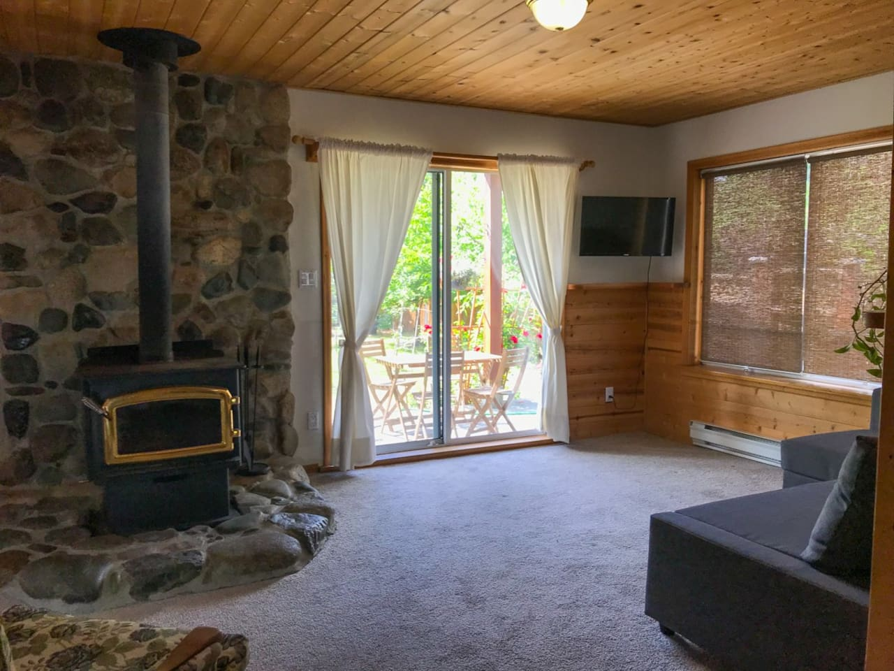 Wood-stove heated living room with garden view, television, and a sofa couch