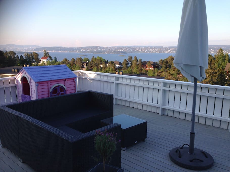 Large terrace with view of the Oslo Fjord and Oslo. With outdoor couch and table.