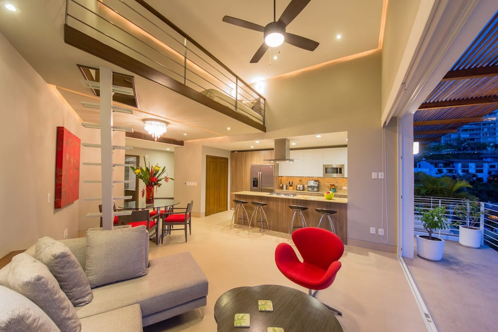 Living room with a glass staircase to the small loft.