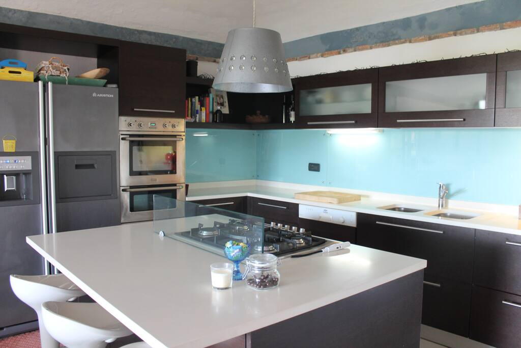 Kitchen island with gas hob, double oven and American style fridge/freezer.
