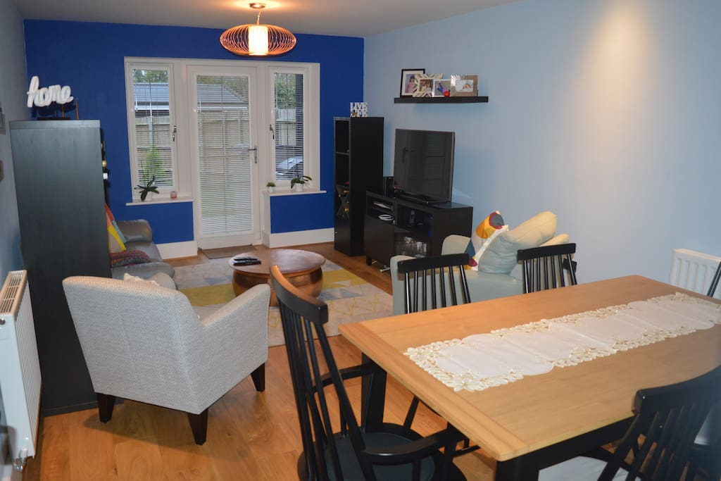 Spacious common lounge with dinning table, TV and access to the garden