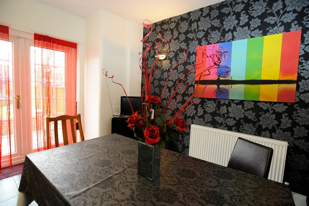 (There is now a larger TV situated on the wall.) Kitchen diner, with TV and entrance to the garden.