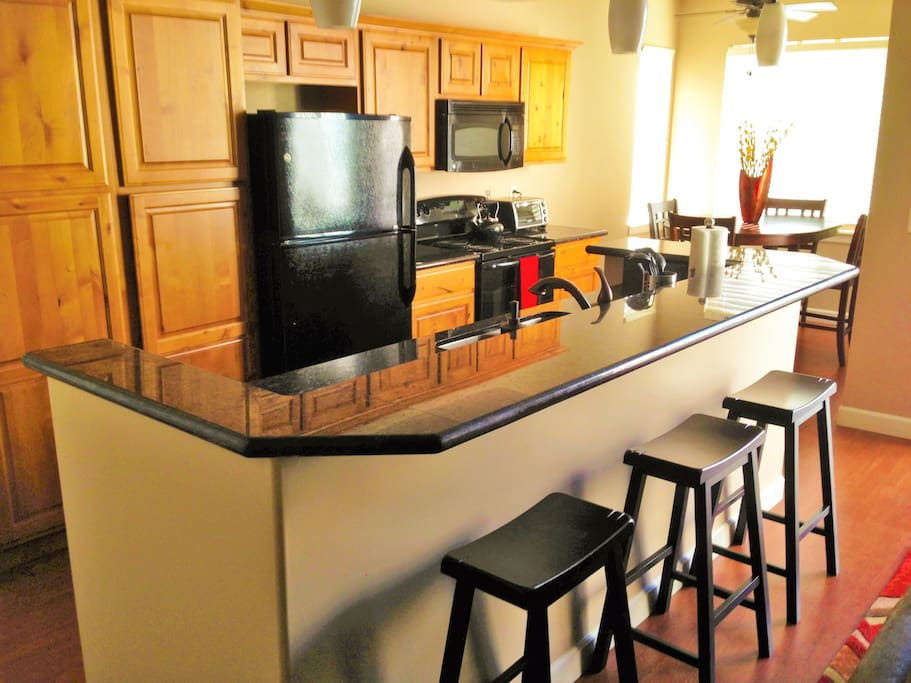 Four bar stools on the granite bar in addition to 6 seats at the dining table