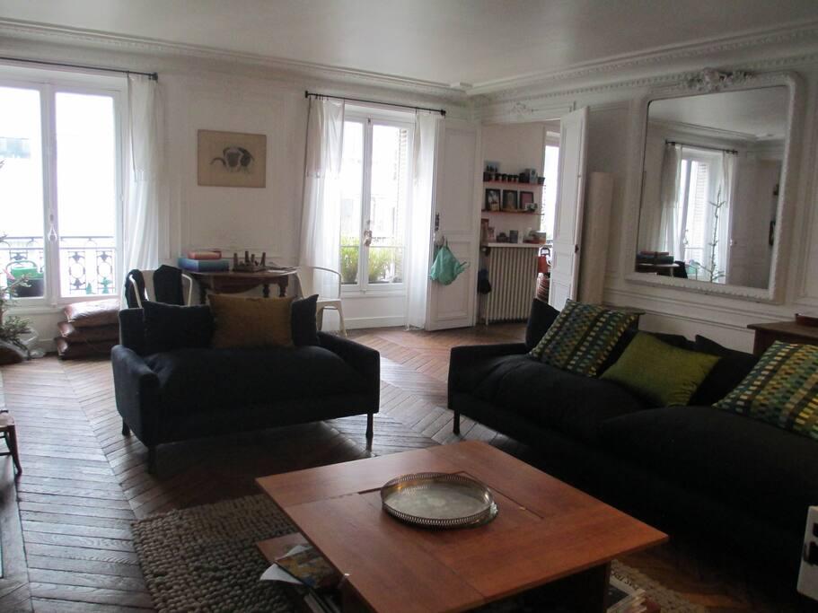 Le salon spacieux et clair, typique du style hausmanien
