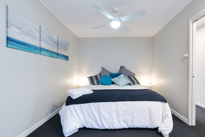 The master bedroom with ultra-comfy king bed and ceiling fan