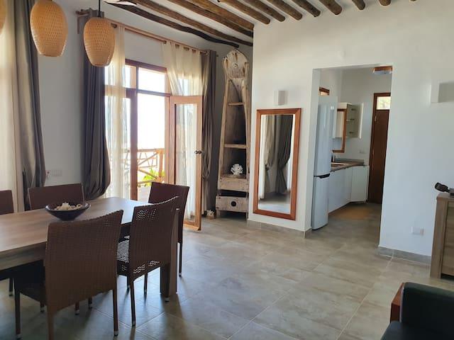Il salotto, grande e arioso, ha il secondo  tavolo da pranzo della casa (utile nelle giornate di vento) e un divano che, all'occorrenza, si trasforma in un comodo letto