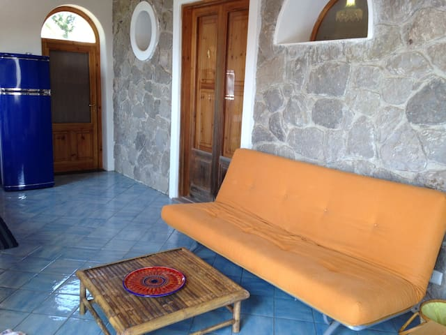The main living area with high ceilings, Italian tile floors, original stone walls and views to the sea and Vulcano Island