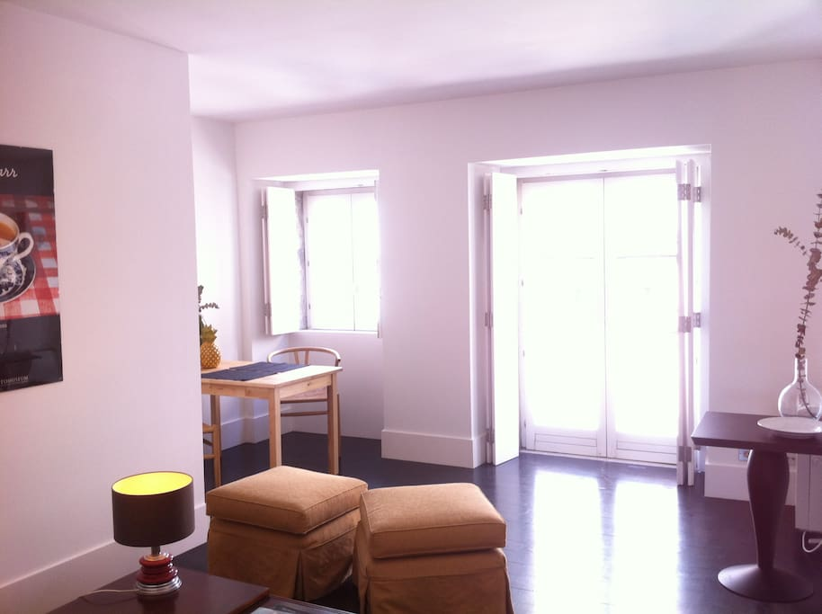 The living room full of light, dining table in front of the window and french balcony on the right!