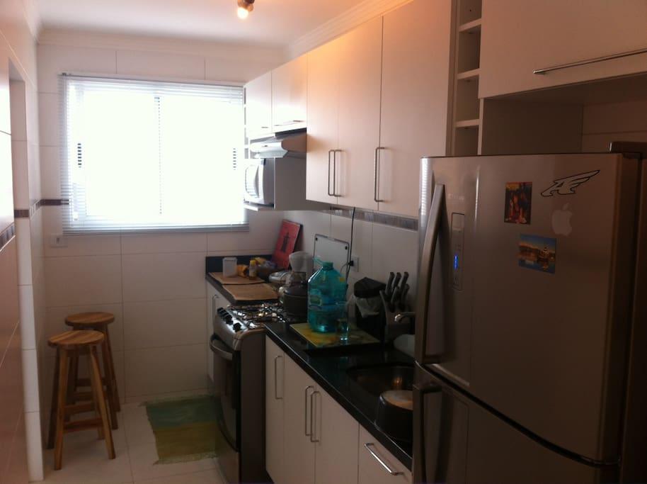 Cozinha completa, com fogão, geladeira, microondas, panelas.