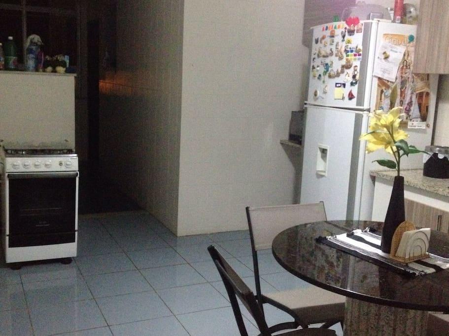 Cozinha com geladeira, fogão,microondas, armários embutidos, tirador de suco, liquidificador e utensílios domésticos.
