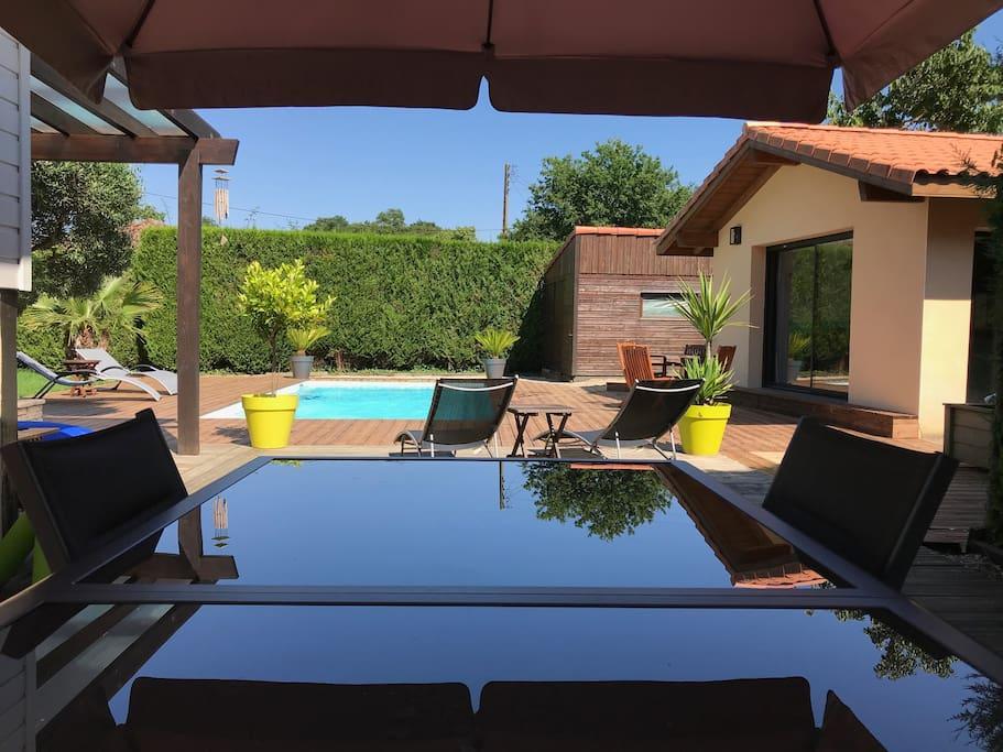 Terrasse avec table à manger pour 12 personnes et vue sur la piscine et le T2