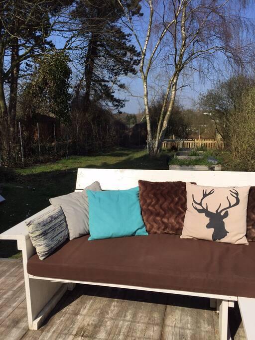 Groot, houten terras en een diepe tuin