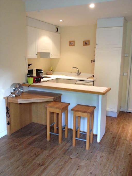 cuisine équipée d'un lave vaisselle, d'un frigo et d'une machine à café nespresso.