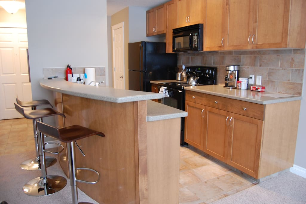 Fully equipped kitchen with breakfast bar and stools.