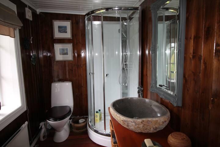 Moderne bad i passende stil. Inneholder toalett, dusj og servant.