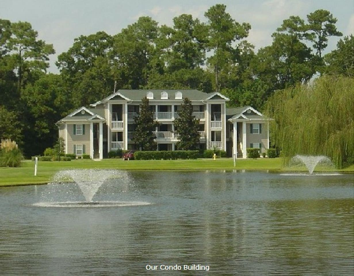 Front of Condo Building Overlooking a Pond With Fountains.  Unit For Rent is on the Ground Floor of the Building.