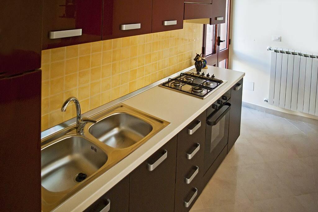 Cucina a vista con frigo, forno e attrezzatura per cucinare