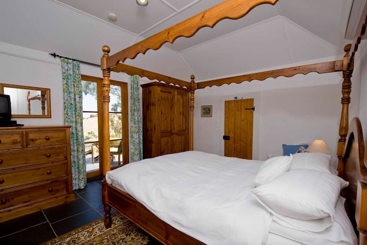 Comfortable queen-size four poster with views over the garden to the ocean.