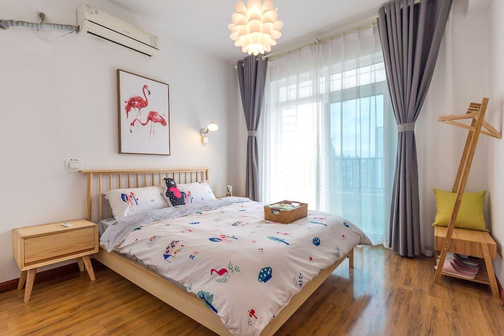 卧室一。房间是干净明亮的配色,床旁边是阳台以及落地推拉门,采光通风都是极好的~!