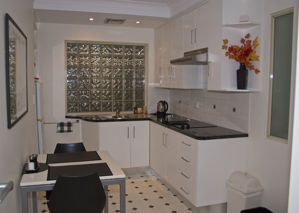 Modern kitchen with full size fridge, microwave and ceramic cooktop.