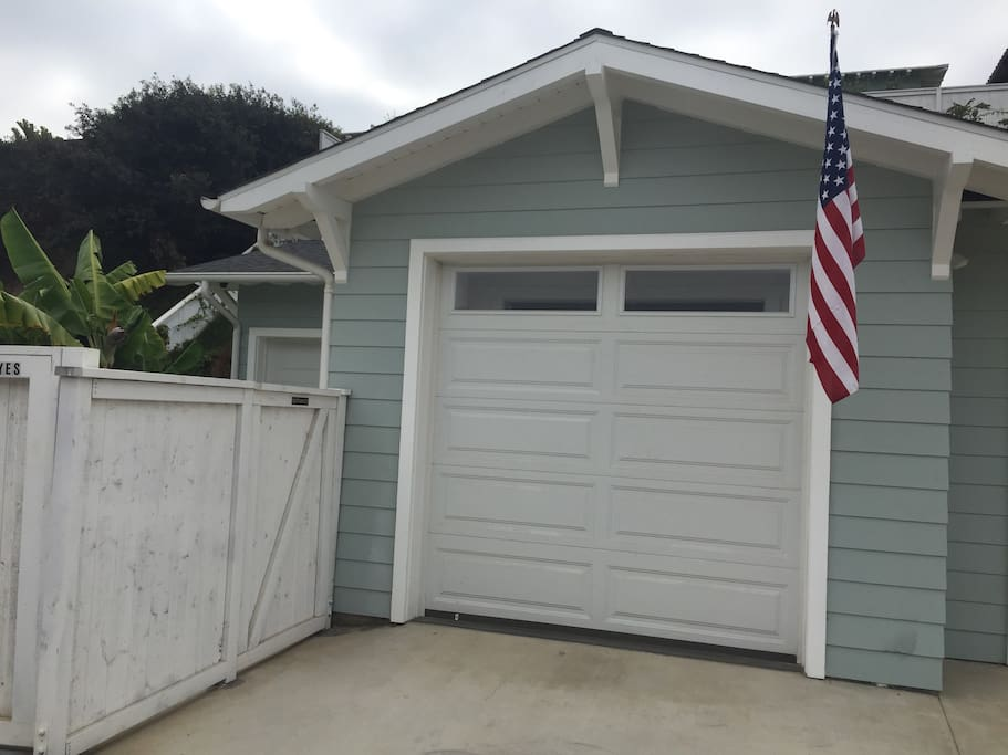 Entrance through gate and parking in front of garage door.
