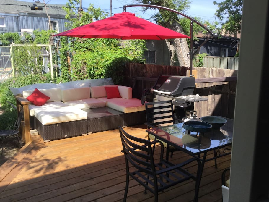 Backyard deck with table for 6 and couches with umbrella.