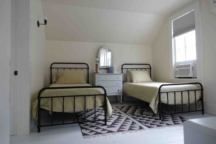 The loft (open bedroom, no door) has two single beds with incredibly supportive and comfortable mattresses. All pillows and linens are feather-free. We have central air but also have a window AC unit in the loft for use on extremely hot nights.