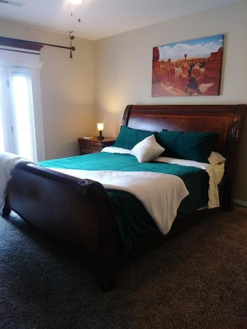 California King Bed (accommodating guests 1 & 2) shown in luxurious emerald and cream decor