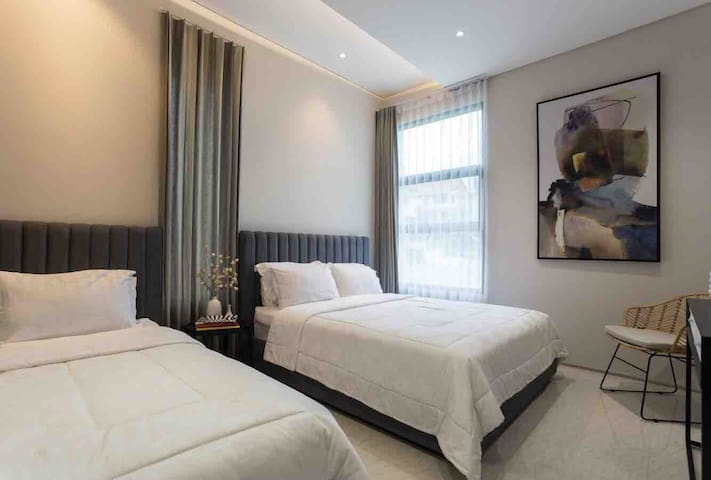 Family bedroom with 1 queen size bed and 1 single size bed, equipped with hotel-quality bedding.
