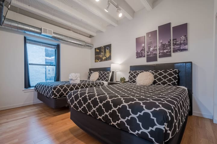 Bedroom 1 offers 2 queen beds, a 40 inch smart television, blackout curtains and a closet. Factory height ceilings and exposed ductwork build the drama of this industrial style loft!