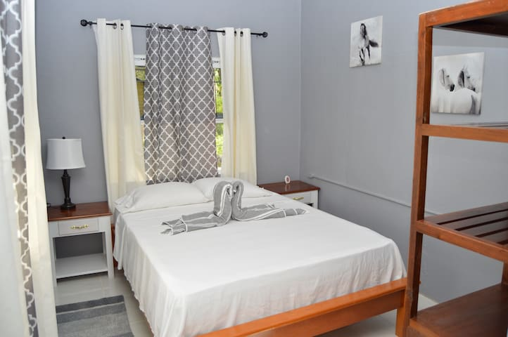 Bedroom 2: Air-conditioned room with a plush queen bed , clothes rack and night stands .
