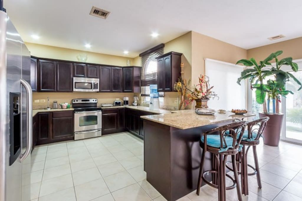 The kitchen has a small breakfast counter and comes equipped with all small and large appliances and plenty of cooking utencils