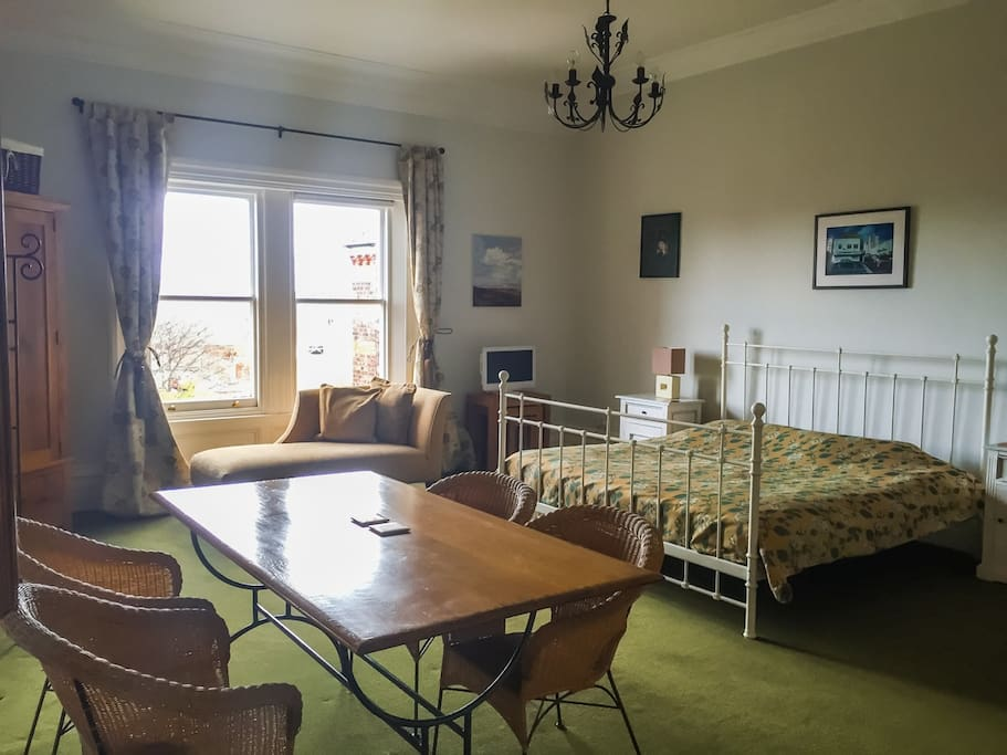 Huge bedroom with table, sofa and king-sized bed