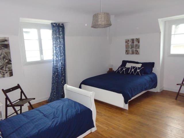 Chambre avec un lit double et un lit gigogne avec un grand placard de rangement