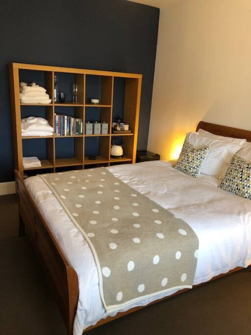 King bed, shelving with guest amenities