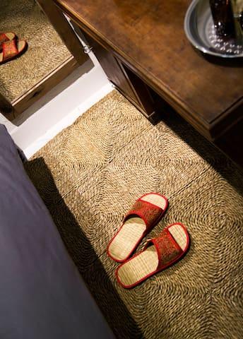 Rattan carpet and rattan slipper in bedroom