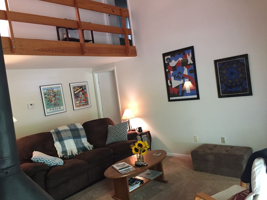 """The main living area with a comfortable couch, a wood-burning fireplace, and a 40"""" HDTV"""